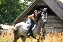 Portrait of beautiful woman on horse near the barn Stock Images
