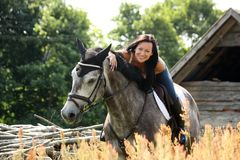 Portrait of beautiful woman on horse near the barn Royalty Free Stock Image