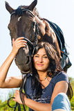 Portrait of a beautiful woman in a horse. Portrait of a beautiful woman in a horse outdoors Stock Photo