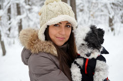 Portrait on beautiful woman hugging her dog in the winter forest Stock Photo