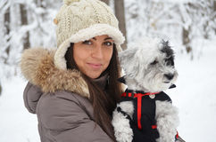 Portrait on beautiful woman hugging her dog in the winter forest Stock Image