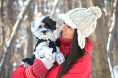 Portrait on beautiful woman hugging her dog in the winter forest Royalty Free Stock Photography