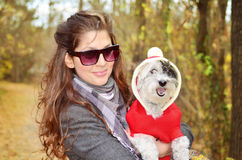 Portrait on beautiful woman hugging her dressed dog Stock Image