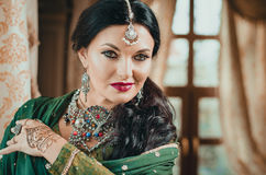 portrait of a beautiful woman in Indian traditional Chinese dress, with her hands painted with henna mehendi. royalty free stock photography