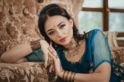 portrait of a beautiful woman in Indian traditional Chinese dress, with her hands painted with henna mehendi. Girl sitting on a l stock images
