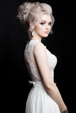 Portrait of beautiful woman in lace dress posing at dark studio. Blonde bride with stylish haircut, earrings with diamonds and acc Royalty Free Stock Photography