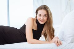 Portrait beautiful woman lay on looking smiling white room royalty free stock images