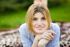 Portrait of a beautiful woman laying in the grass with a smile Royalty Free Stock Images
