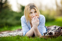 Portrait of a beautiful woman laying in the grass with a smile Stock Photos