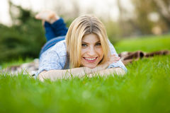 Portrait of a beautiful woman laying in the grass with a smile Royalty Free Stock Image