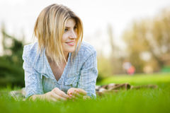 Portrait of a beautiful woman laying in the grass with a smile Royalty Free Stock Photos