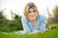 Portrait of a beautiful woman laying in the grass with a smile Stock Image