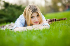 Portrait of a beautiful woman laying in the grass with a smile Royalty Free Stock Photo
