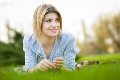 Portrait of a beautiful woman laying in the grass with a smile Royalty Free Stock Photography