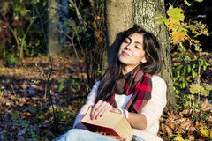 Portrait of a beautiful woman leaning on a tree with book in the autumn park Stock Photography