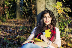 Portrait of a beautiful woman leaning on a tree with book in the autumn park Stock Image