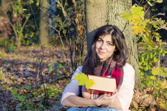 Portrait of a beautiful woman leaning on a tree with book in the autumn park Royalty Free Stock Photography