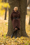 Portrait of a beautiful woman leaning on a tree trunk Royalty Free Stock Photo