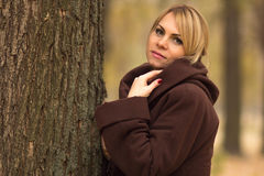 Portrait of a beautiful woman leaning on a tree trunk Stock Images
