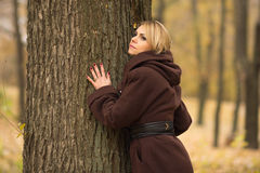 Portrait of a beautiful woman leaning on a tree trunk Royalty Free Stock Images