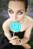 Portrait of beautiful woman with lollipop candy sitting on meadow Stock Images