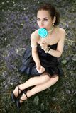 Portrait of beautiful woman with lollipop candy sitting on meadow Royalty Free Stock Image
