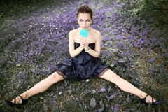 Portrait of beautiful woman with lollipop candy sitting on meadow Stock Photos