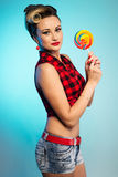 Portrait of beautiful woman with lollipop, dressed in pin-up style. stock photography