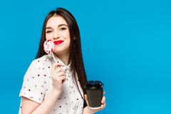 Portrait of beautiful woman with lolly isolated on blue background. Portrait of beautiful brunette girl with red Royalty Free Stock Photography