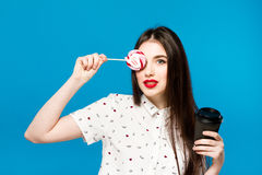 Portrait of beautiful woman with lolly isolated on blue background. Portrait of beautiful brunette girl with red Royalty Free Stock Image