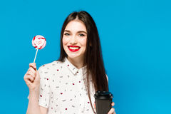 Portrait of beautiful woman with lolly isolated on blue background. Portrait of beautiful brunette girl with red Stock Image