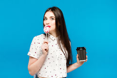 Portrait of beautiful woman with lolly isolated on blue background. Portrait of beautiful brunette girl with red Royalty Free Stock Images