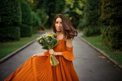 Portrait of beautiful woman in long orange dress. With bouquet of flowers on the background of road and trees Stock Photos