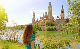 Portrait of beautiful woman looking at Cathedral Basilica of Our Lady of the Pillar, spanish landmark in Zaragoza, Spain royalty free stock image