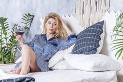 Woman with wine on the bed royalty free stock photos