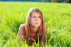 Portrait of beautiful woman lying on green grass Stock Image