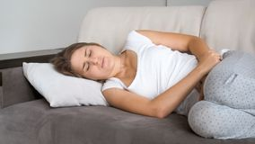 Portrait of beautiful young woman lying on sofa and suffering from pain in stomach. Portrait of beautiful woman lying on sofa and suffering from pain in stomach Stock Images
