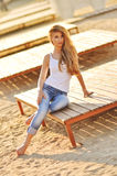 Portrait of a beautiful woman with magnificent hair in a white top and stylish jeans Stock Photography