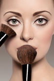 Portrait of a beautiful woman with a make up brush Royalty Free Stock Photography
