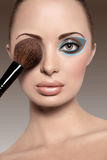 Portrait of a beautiful woman with a make up brush Stock Photos