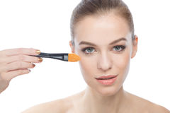 Portrait of the beautiful woman with make-up brush, over a white Stock Images