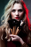 Portrait of beautiful woman with makeup brushes royalty free stock image