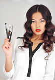 Portrait of a beautiful woman with makeup brushes near face Stock Image