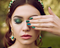 Portrait of beautiful woman, makeup and manicure in the same style, jewelry with precious stones. Makeup and manicure stock images
