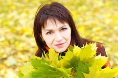 Portrait of beautiful woman with maple leaves in autumn Royalty Free Stock Images