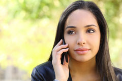 Portrait of a beautiful woman on the mobile phone in a park. With a green unfocused background Royalty Free Stock Photos