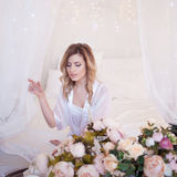 Portrait of beautiful woman model with fresh daily makeup and romantic wavy hairstyle. Girl received flowers as a gift Royalty Free Stock Images