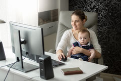 Portrait of beautiful woman with 9 month baby working at home stock photos