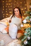 Portrait of a beautiful woman near the Christmas tree cute smiling royalty free stock photography
