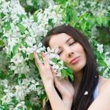 Portrait of beautiful woman near a flowering tree Stock Photo